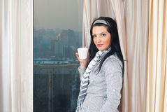 Woman with cup in front of window Stock Photos