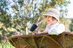 Woman  with cup in the garden. Woman in hat sitting in the garden  and holding a  cup Stock Image