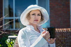 Woman  with cup  in the garden. Woman sitting  in the garden  and holding a  cup of coffee Stock Photo