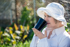 Woman  with cup in the garden. Woman sitting  in the garden  and holding a  cup of coffee Royalty Free Stock Photography