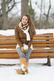 Woman with cup of hot beverage sitting on bench in winter park Royalty Free Stock Images