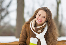 Woman with cup of hot beverage sitting on bench in winter park Royalty Free Stock Photo
