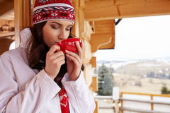 Woman with cup of hot chocolate on mountain ski resort Stock Image