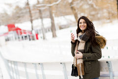 Woman with a cup of hot drink on  cold winter outdoors Royalty Free Stock Images