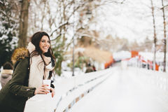 Woman with a cup of hot drink on  cold winter outdoors Stock Image