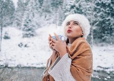 Woman with cup of hot drink in snow forest Stock Image
