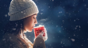 Woman with a cup of hot tea. Happy young woman with a cup of hot tea on snowy winter walk in nature. Concept of frost winter season Royalty Free Stock Photos