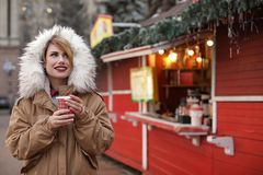 Woman with cup of mulled wine at winter fair. Space royalty free stock photos