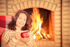 Woman with cup near fireplace Stock Images