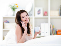 Woman with cup speaking by mobile phone Stock Photography