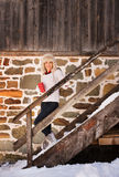 Woman with cup standing on stairs of cosy mountain house Royalty Free Stock Photos
