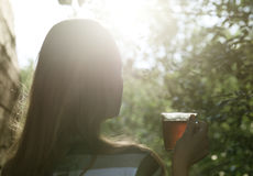 Woman with cup of tea in evening sunlight Stock Photography