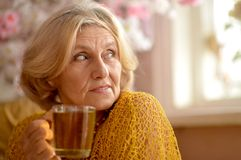 Woman with cup of tea. Happy smiling elder woman with cup of tea royalty free stock photos