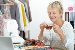 Woman with a cup of tea in his sewing worshop Royalty Free Stock Photo