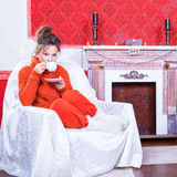 Woman with a cup of tea inside a red vintage room next to a chri Stock Photos