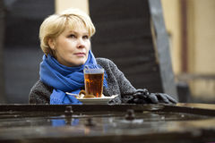 Woman and a cup of tea. Woman sitting on the terrace of a cafe. It'S Cold. The rain is falling. Soon she will warm up by drinking tea Royalty Free Stock Image
