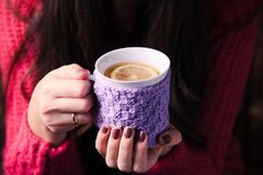 Woman with cup of tea. Woman is holding a knitted cup of tea with lemon stock photography