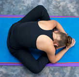Woman curled up in bound angle forward fold. Looking down on an athletic brown haired woman doing yoga exercise Bound Angle Forward Bend pose on yoga mat in Royalty Free Stock Photos