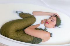 Woman curled up in milk bath royalty free stock photos
