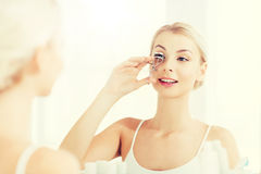 Woman with curler curling eyelashes at bathroom Royalty Free Stock Images