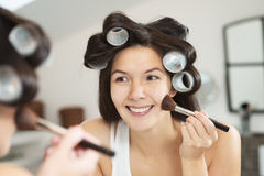 Woman in curlers applying makeup Stock Image