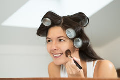 Woman in curlers applying makeup Stock Photo