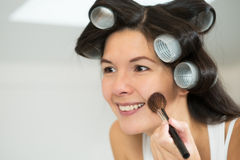 Woman in curlers applying makeup Royalty Free Stock Images