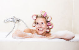 Woman with curlers in bathtub Stock Photos