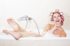 Woman with curlers in bathtub. Blond woman sitting in bathtub with curlers in her hair Royalty Free Stock Photography