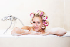 Woman with curlers in bathtub Stock Image