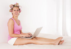 Woman with curlers in bed with laptop Stock Photos