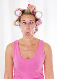Woman with curlers. Blond woman with pink curlers making faces stock images
