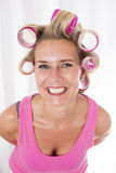 Woman with curlers. Blond woman with pink curlers is smiling royalty free stock image