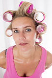 Woman with curlers. Blond woman with pink curlers is smiling royalty free stock images