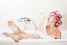 Woman with curlers. Blond woman sitting in bathtub with curlers in her hair royalty free stock photography
