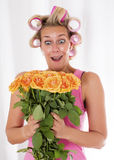 Woman with curlers and a bouquet of roses Royalty Free Stock Image