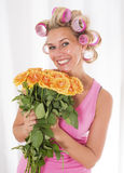 Woman with curlers and a bouquet of roses Stock Image