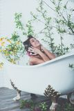 Woman with curlers on hair sit in bath, body care. royalty free stock images