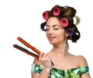 Woman with curlers hold hair curling ironing tool. Isolated on a white background Royalty Free Stock Images