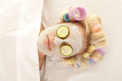 Woman curlers mask close up. A woman is laying with curlers and a cream face mask royalty free stock image