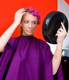 Woman with curlers and mirror. Woman in salon with curlers in her hair look herself in mirror Stock Photos