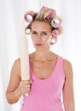 Woman with curlers and a rolling pin Stock Image