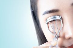 A woman is curling eyelashes stock image