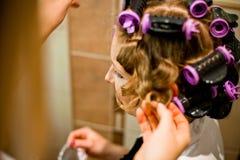 Woman curling hair Stock Image