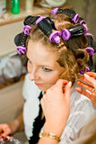 Woman curling hair Stock Images