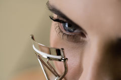 Woman curling her eyelashes Royalty Free Stock Image