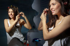 Woman curling her hair stock photos