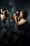 Woman curling her hair royalty free stock photography