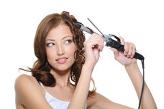 Woman curling her hair with roller royalty free stock image