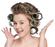 Woman curling her hair with roller Stock Photos